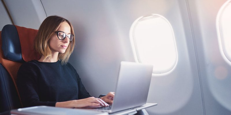 A woman on an airplane uses her computer during flight