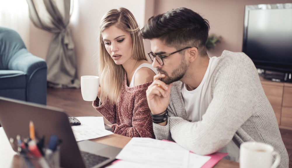 A young couple review their finances with paperwork and a laptop