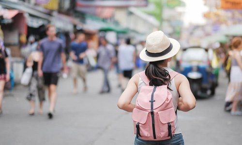 A woman with a pink backpack walks down a busy street