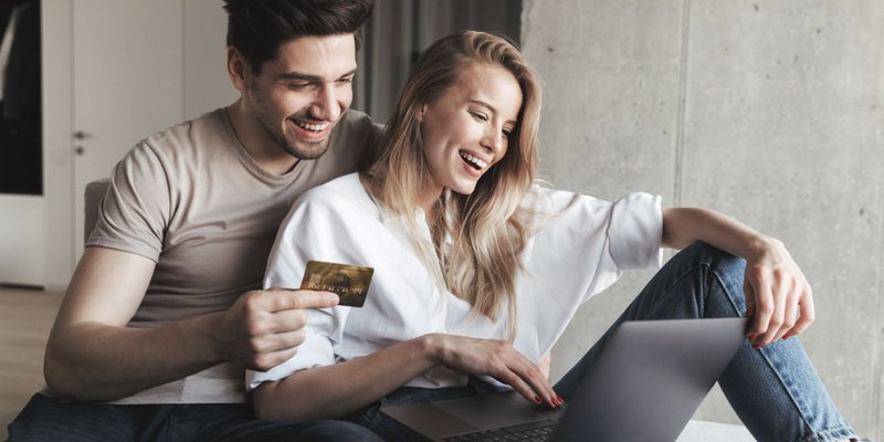 A young man holds a credit card while a young woman holds a laptop computer