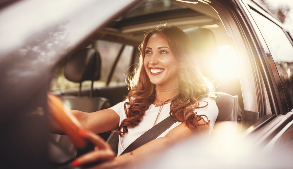 A young woman drives with the sun reflecting behind her