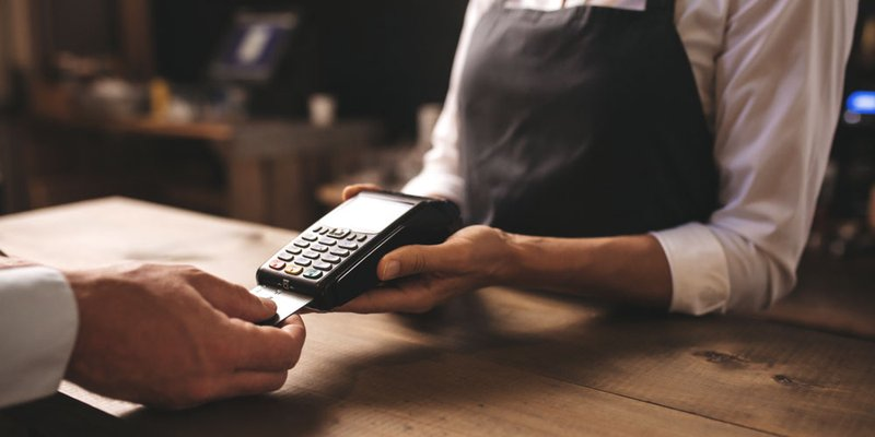 A hand inserts a credit card into a point of sale terminal at a shop