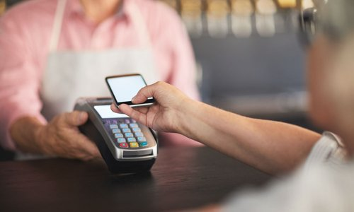 A senior uses their smartphone to pay on the point of sale terminal