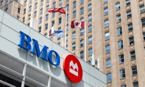 A BMO branch with Canadian flags waving in the wind