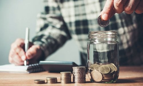 A hand drops coins into a mason jar while keeping track of savings with a notepad and calculator