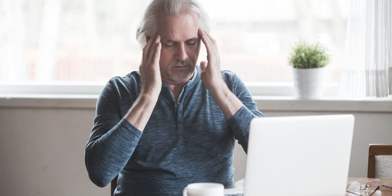 An older man hold his temples as if he has a headache