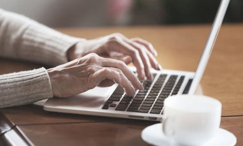 A close-up of an older person typing on the computer