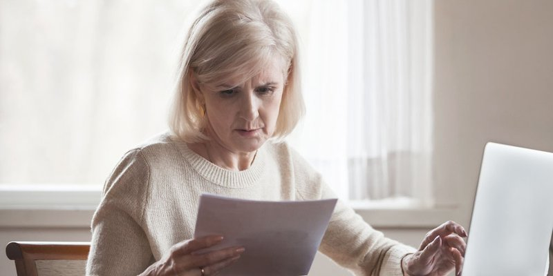 An older woman looking worried at documents