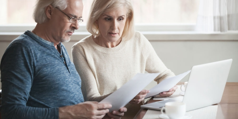 Two seniors sit together and review their finances