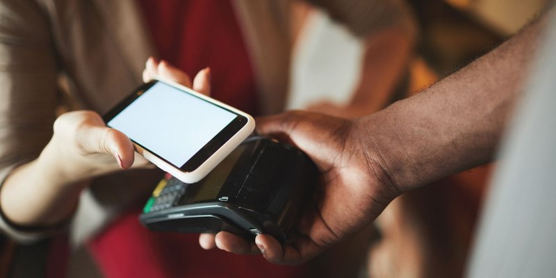 A woman taps her smartphone to pay