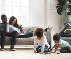 Two parents type away on a laptop while two children colour on the floor