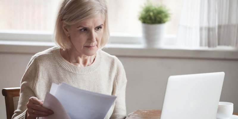 An older woman looking through documents as she works on her laptop
