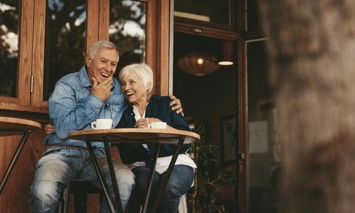 A senior couple laughing and enjoying coffee at a cafe
