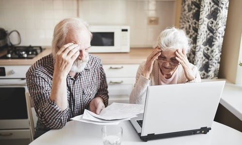 A senior couple look worried as they review their monthly bills