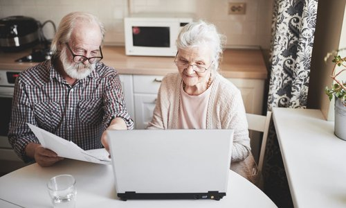 An older couple reviewing paperwork and working on a laptop