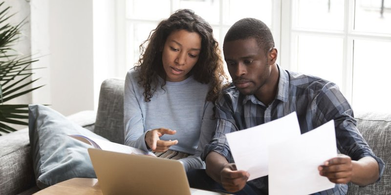 A young couple look intently at a series of papers and something on the laptop in front of them