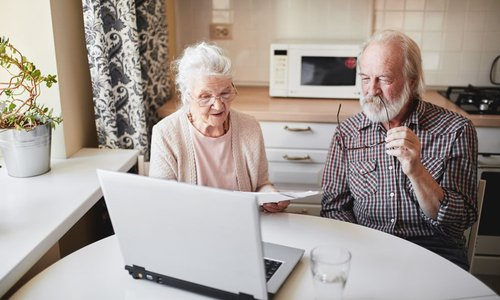 An older man takes off his glasses as his wife shows him paperwork