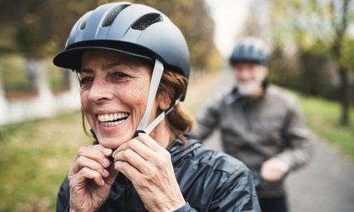 A close-up of a woman buckling her helmet