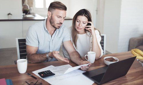 A man looks frustrated as he talks to his partner about the monthly bills