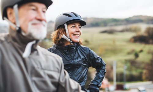 An older man and woman take a break from riding their bikes
