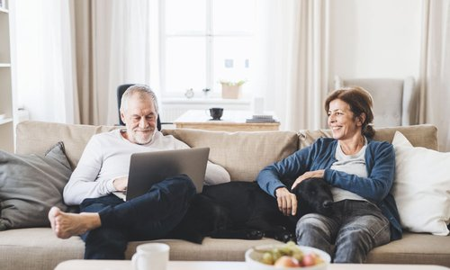 An older man sits with his laptop while an older woman plays with a dog on the couch