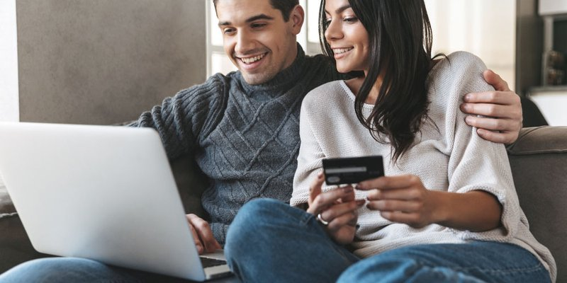 A young couple shop online together using a credit card