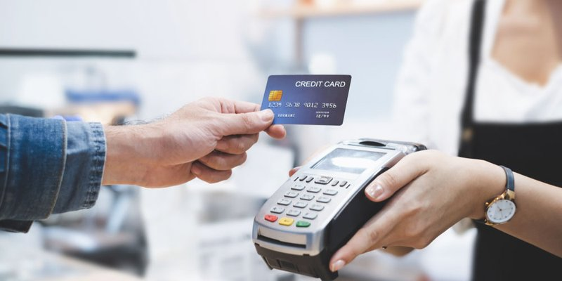 A person taps their credit card to pay at a store