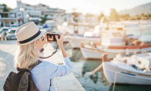 A woman takes a photo of the boats in the harbour
