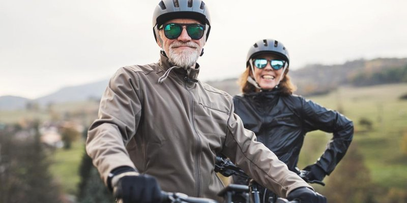 An older couple smiles and wears sunglasses as they get ready to ride their bikes
