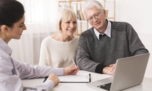 A senior couple reviews documents with a financial advisor