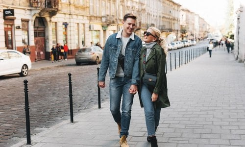 A young couple walk happily down the street in fall clothes