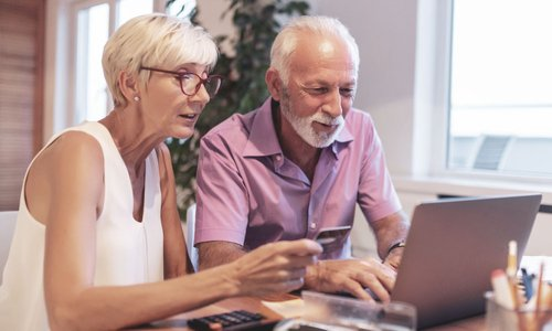 A senior couple use their credit card to shop online