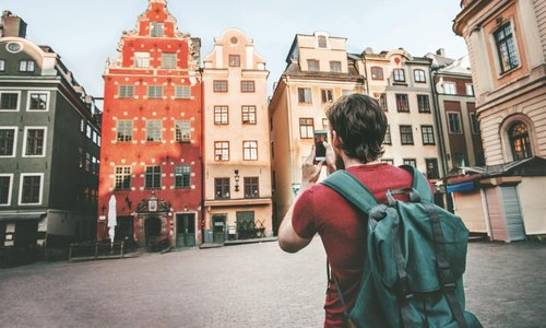 A man takes a picture of the colourful houses on the street