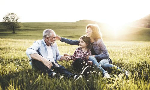 An older man and woman sit with a young child in a field