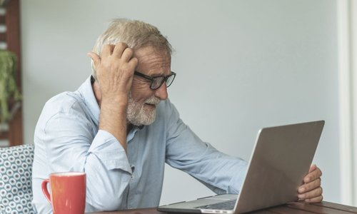An older man scratches his head as he sits at his laptop