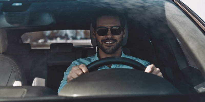 A male driver wears sunglasses in the driver's seat of a car