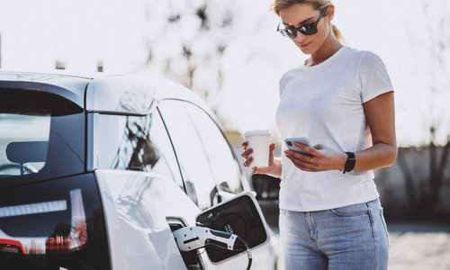 A woman waits for her electric vehicle to charge while using her phone and holding a coffee