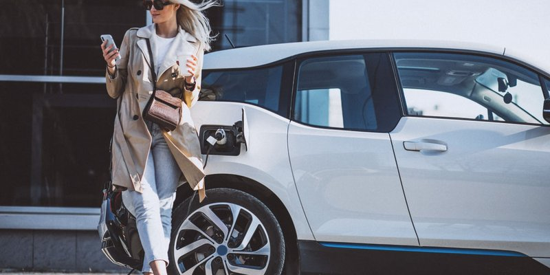 A woman leans against her electric vehicle while it charges