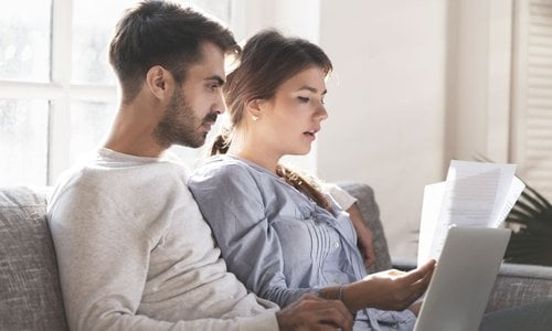 A man and woman review paperwork as they sit on the couch