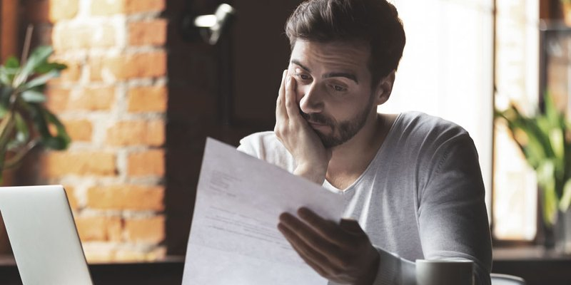 A man looks upset as he reviews a document