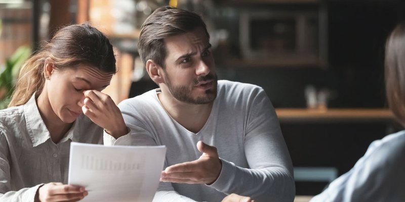 A man and woman look very upset and overwhelmed while speaking with someone about a document