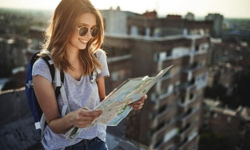A young woman stands on a rooftop and reads a map