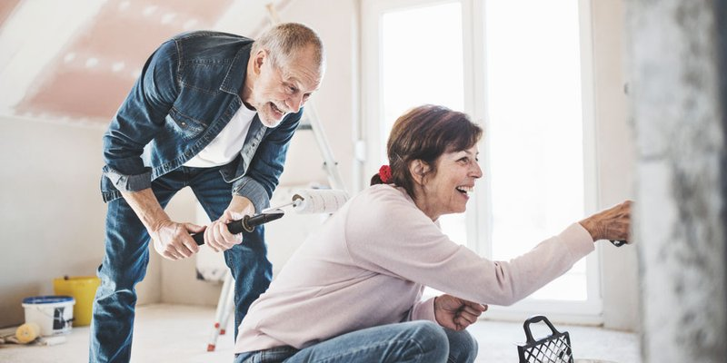 An older man and woman laugh as they paint their home