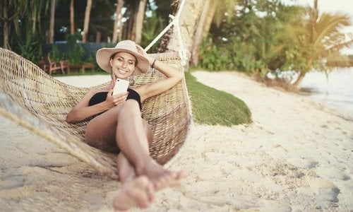 A woman lounges in a hammock on the beach