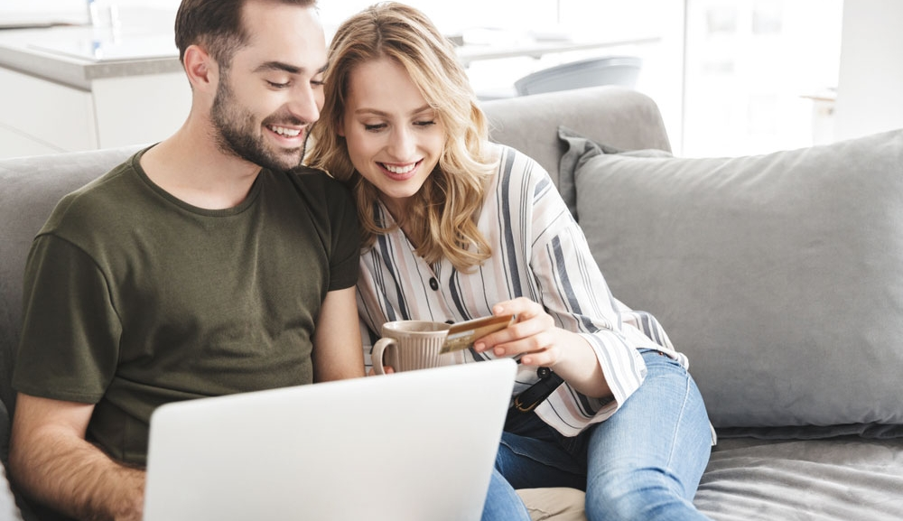 A young couple shop online using their credit card while sitting on the couch