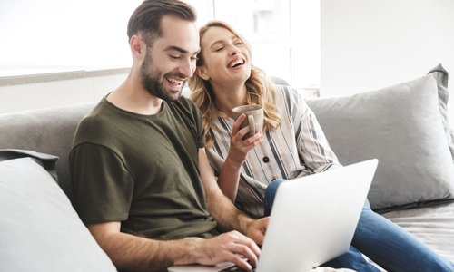 A couple laugh together as they shop online