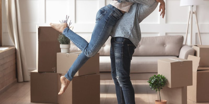 A man holds a woman up in the air in a big hug surrounded by moving boxes
