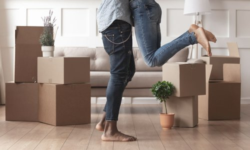 Two people hug surrounded by moving boxes