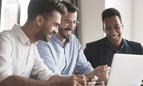 Three men laugh and work together at a computer