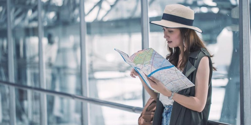 A woman reads a map at the airport